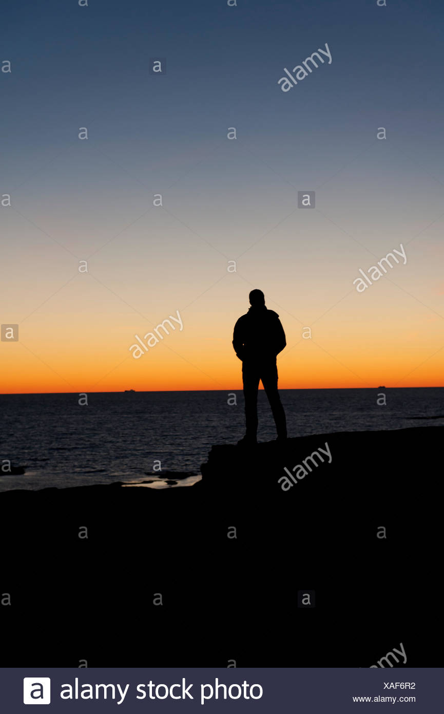 La Suède, Bohuslan, Silhouette of man standing on beach at Dusk Photo Stock