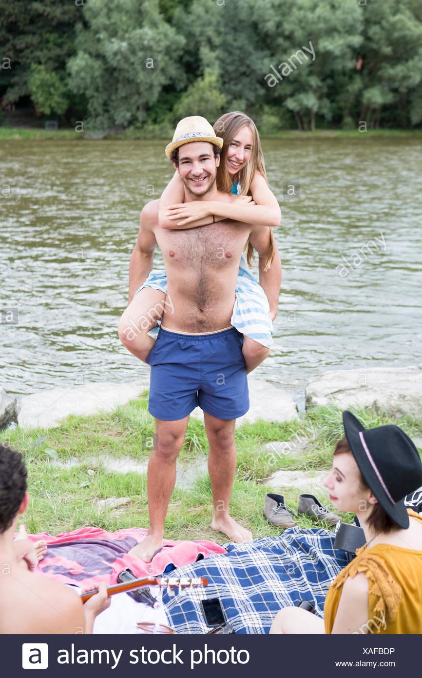 Young man giving girlfriend piggyback sur la rive Photo Stock