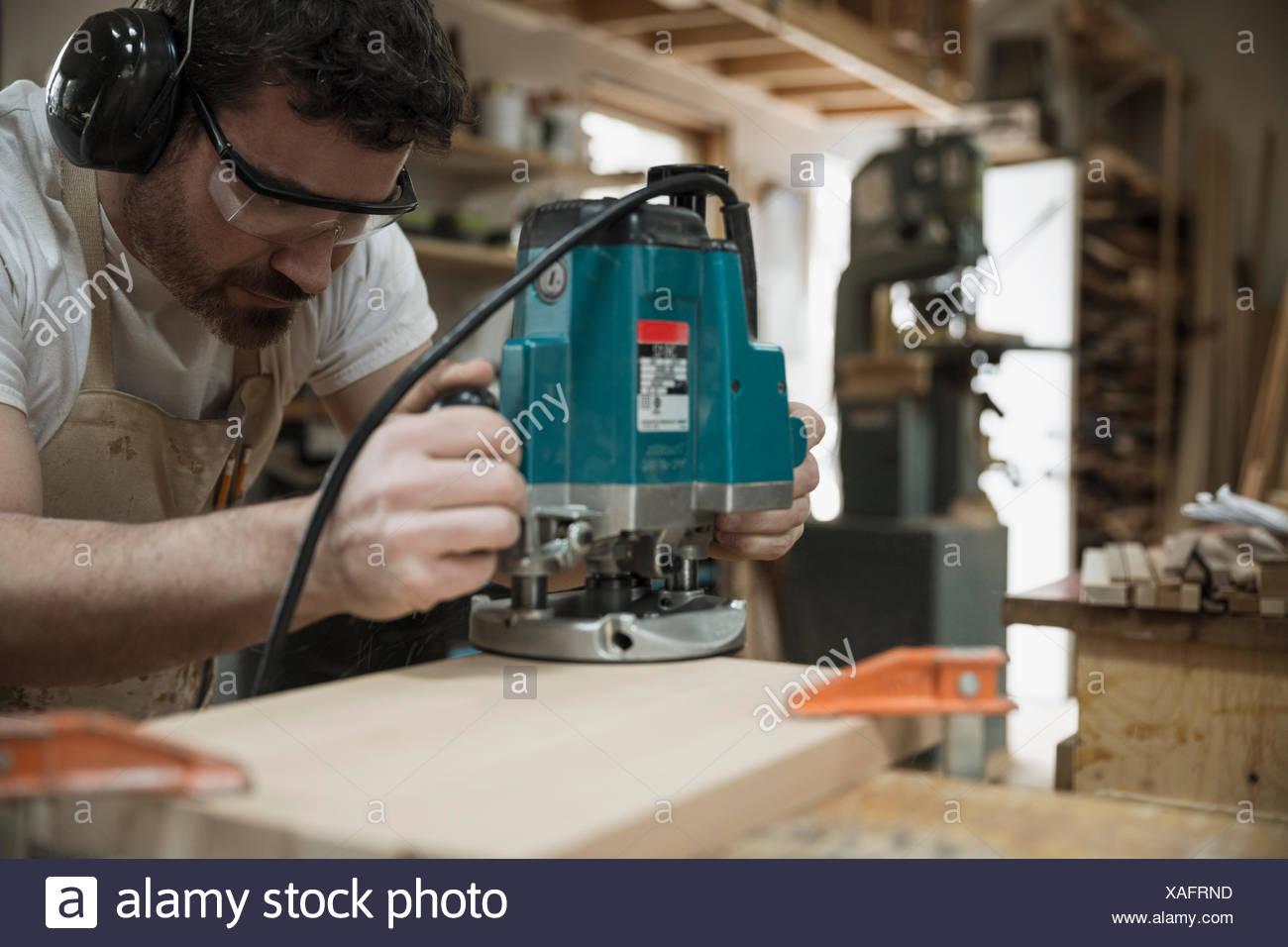 Carpenter à l'aide de scie à main dans l'atelier Photo Stock