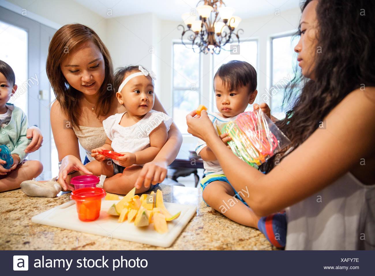 Les femmes nourrir bébé fils et fille fruit sur compteur de cuisine Banque D'Images