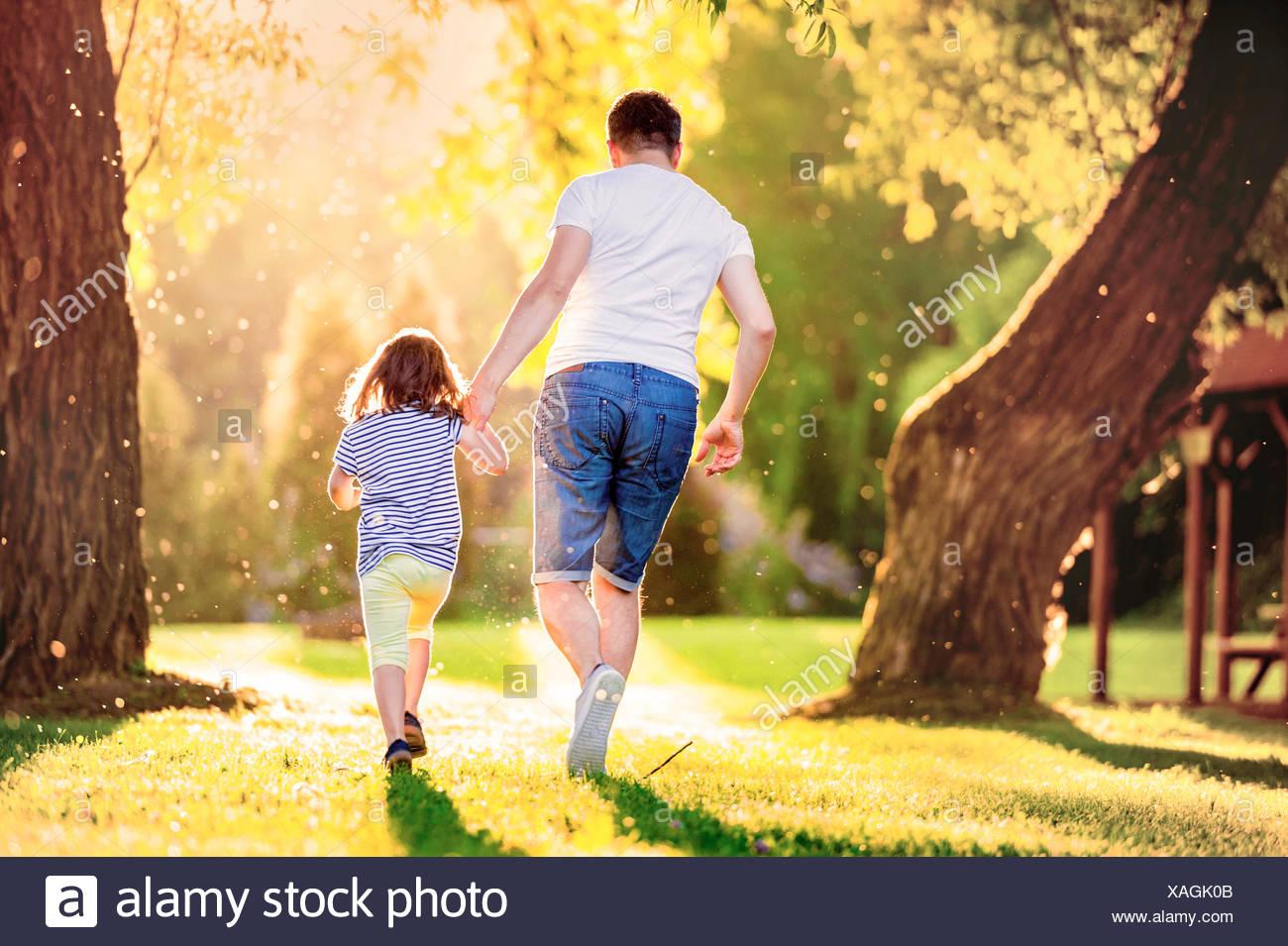 Vue arrière de père et sa petite fille s'exécutant sur une prairie dans le parc Photo Stock
