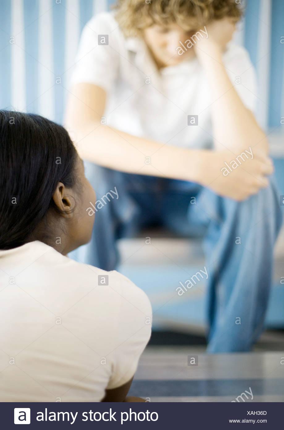 Jeune garçon assis, la tête en bas, en face de teen girl Banque D'Images