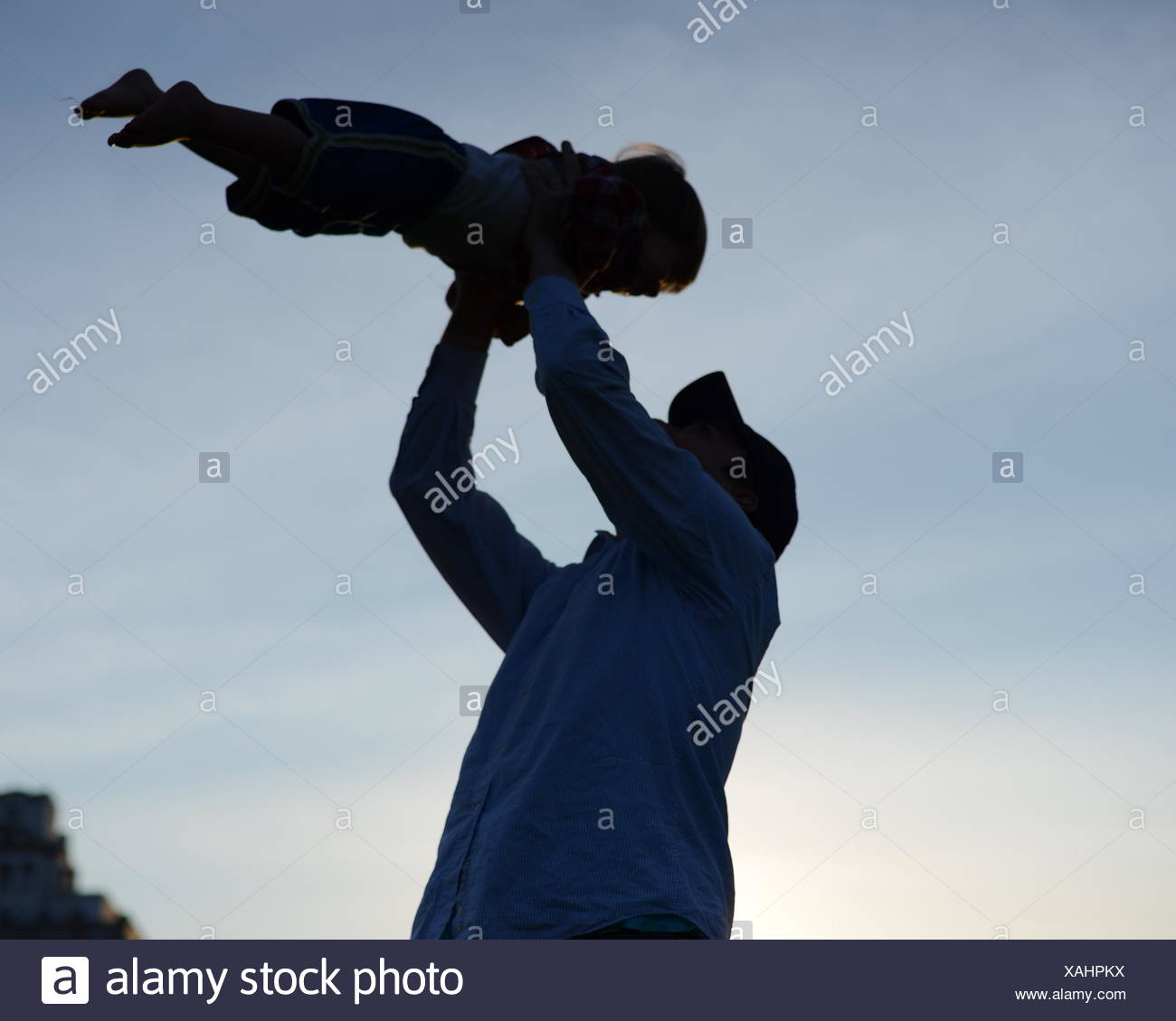 Low Angle View Of Man Carrying Baby contre le ciel Photo Stock