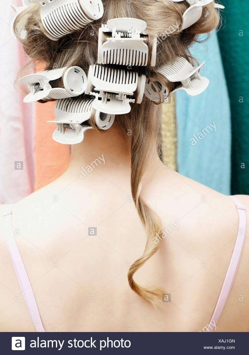 Femme portant des bigoudis avec une seule mèche de cheveux pendant vers le bas Photo Stock