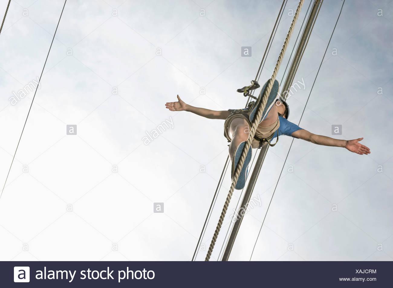 L'équilibrage de l'adolescent dans une escalade de rocher Photo Stock