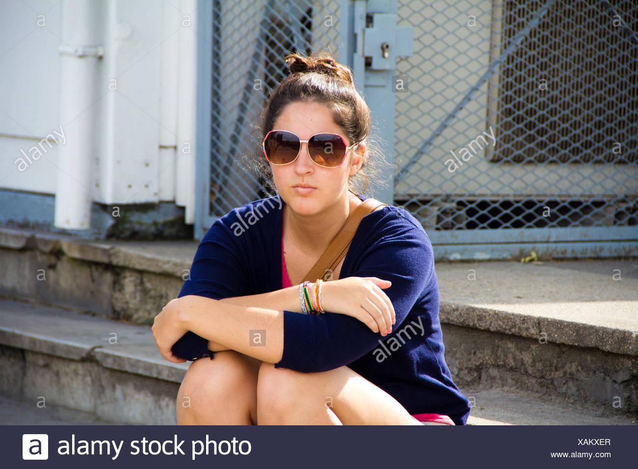 Femme portant des lunettes de soleil assis sur un pas Photo Stock
