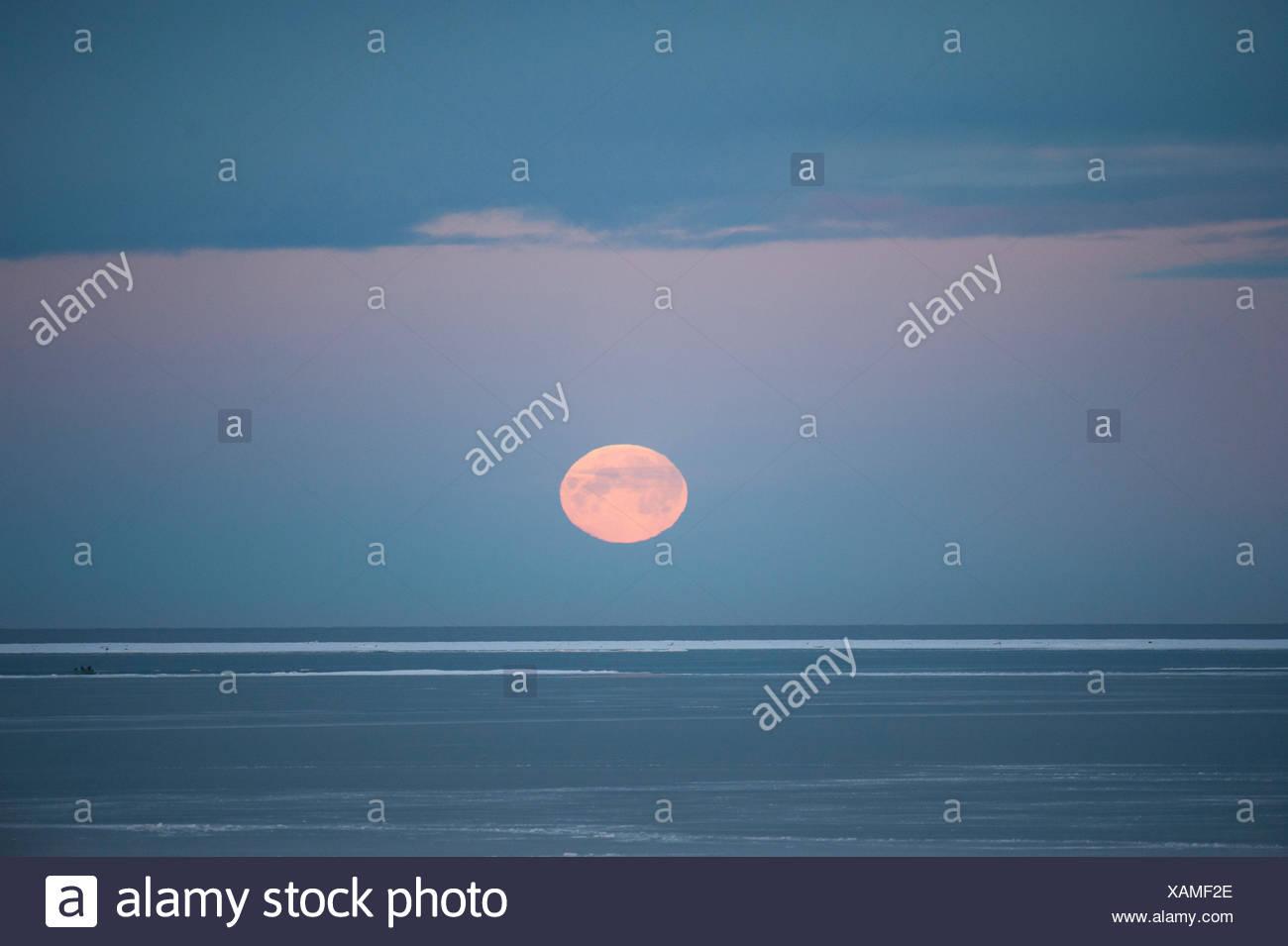 La pleine lune d'automne au-dessus de l'horizon au-dessus de la mer de Beaufort, au large de la côte de l'Arctique, Alaska Photo Stock