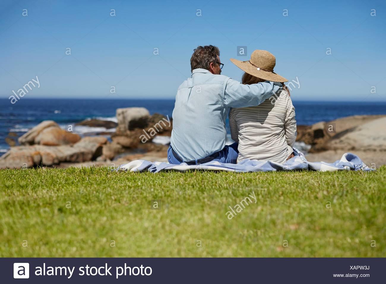 Parution du modèle. Senior couple on picnic blanket, l'homme avec le bras autour des épaules de la femme. Photo Stock