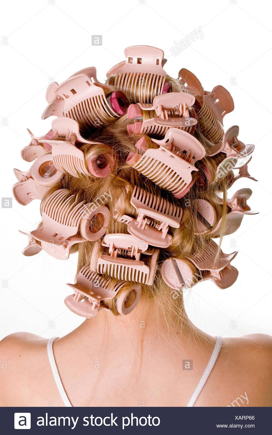 Belle jeune fille, c'est avoir les bigoudis sur la tête. Photo Stock