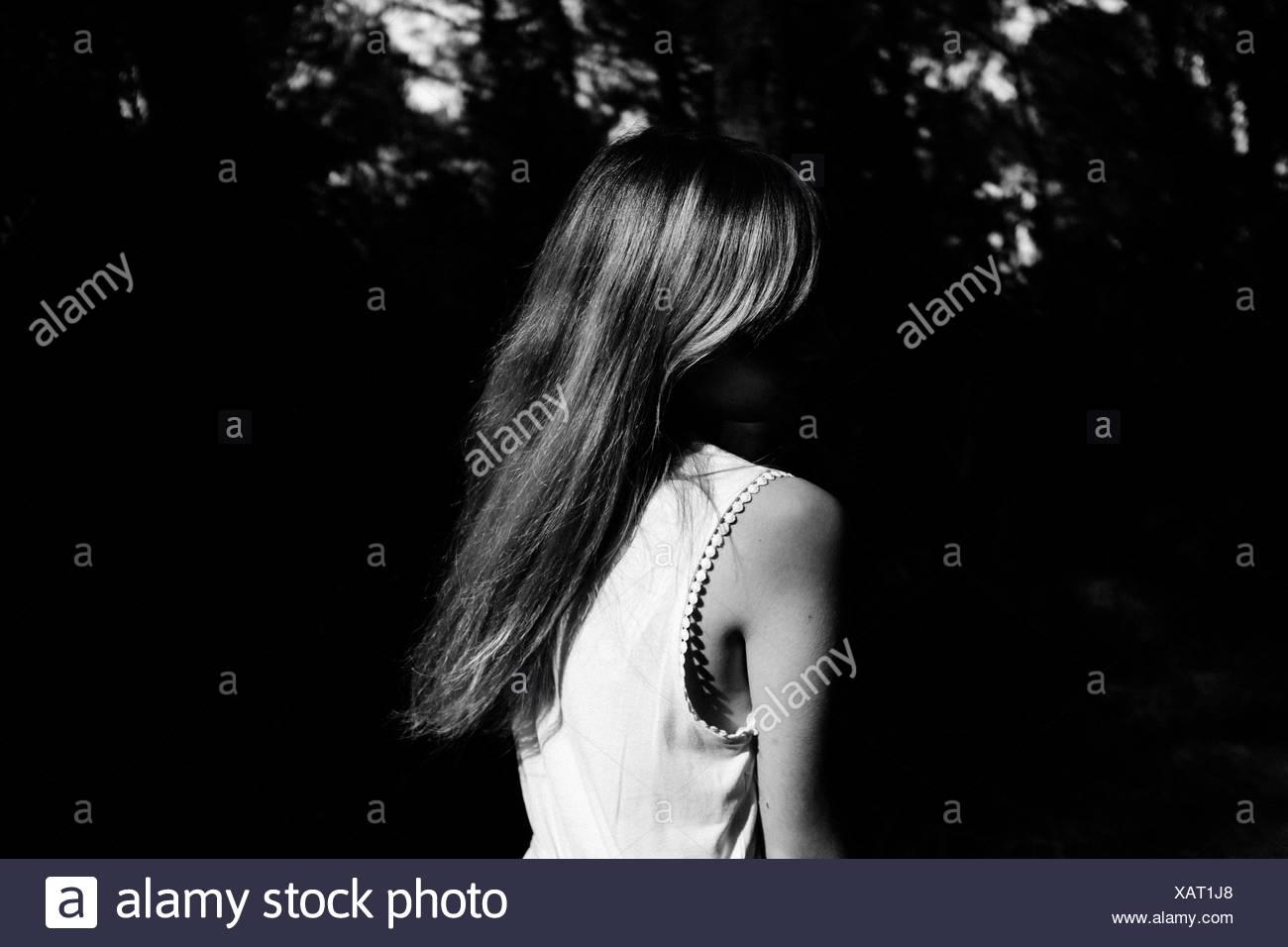Vue arrière d'une femme contre les plantes sombre Photo Stock