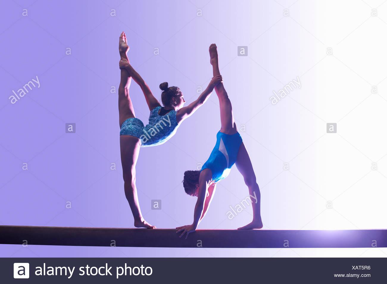 Deux jeunes gymnastes effectuant sur poutre Photo Stock