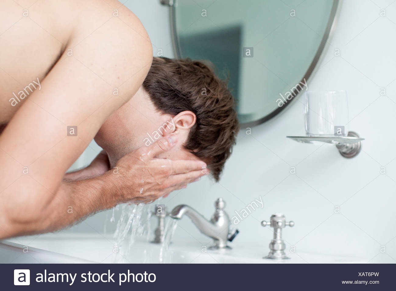 L'homme face au lavabo de la salle de lavage Photo Stock
