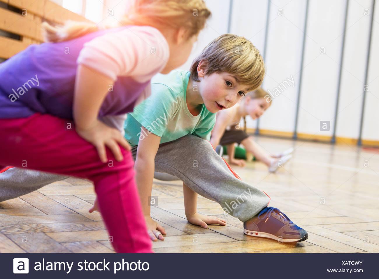 Enfants stretching, jambes pliées, se penchant vers l'avant Banque D'Images