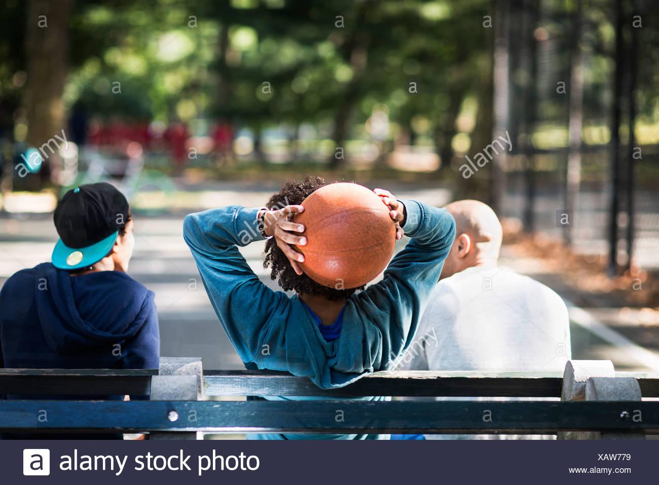 Les jeunes hommes assis sur le parc, un holding basketball Photo Stock