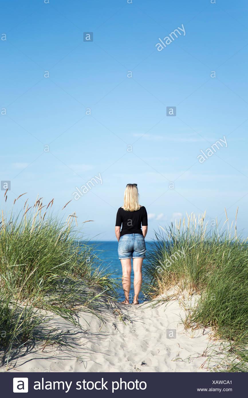 La Suède, Skane, Soderslatt Beddinge,, vue arrière du blond woman standing on beach et à la recherche en mer Photo Stock
