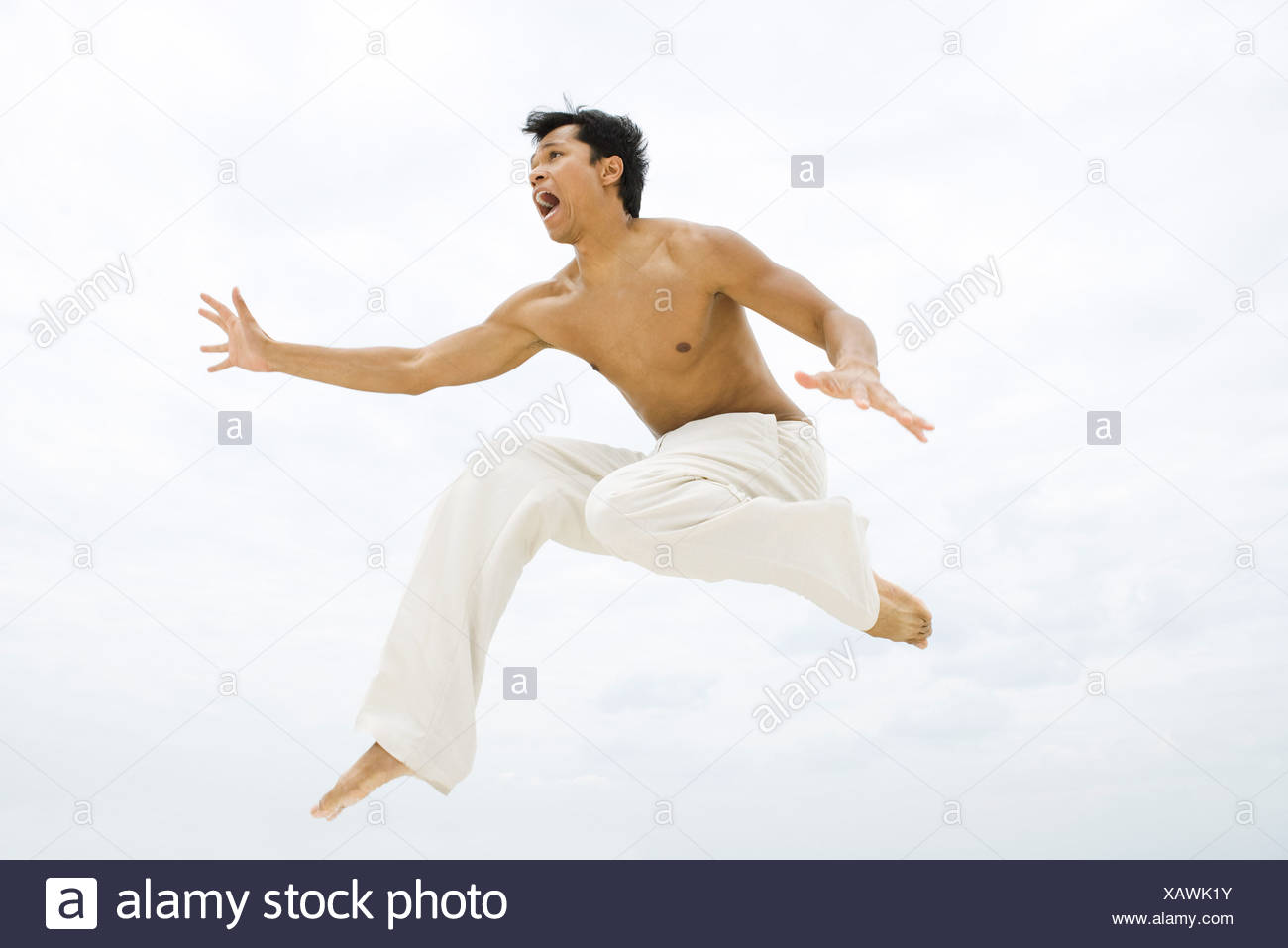 L'homme en sautant en l'air, side view Photo Stock