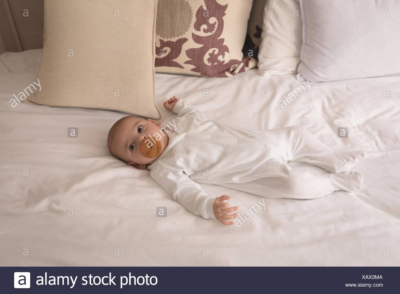 Mignon petit bébé avec tétine en bouche de dormir sur le lit Banque D'Images
