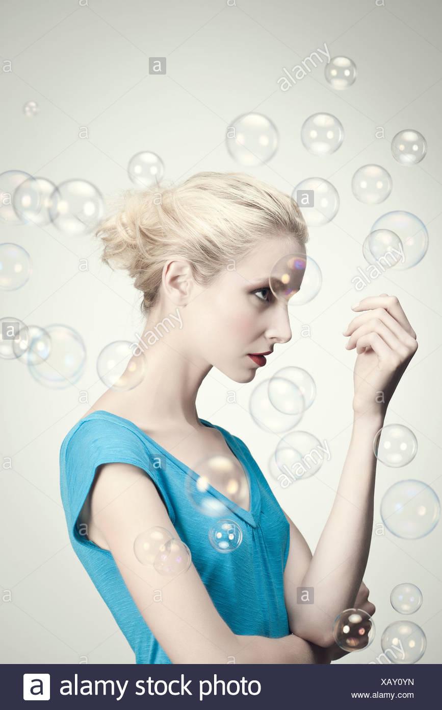 Jeune femme entourée par des bulles, portrait Photo Stock