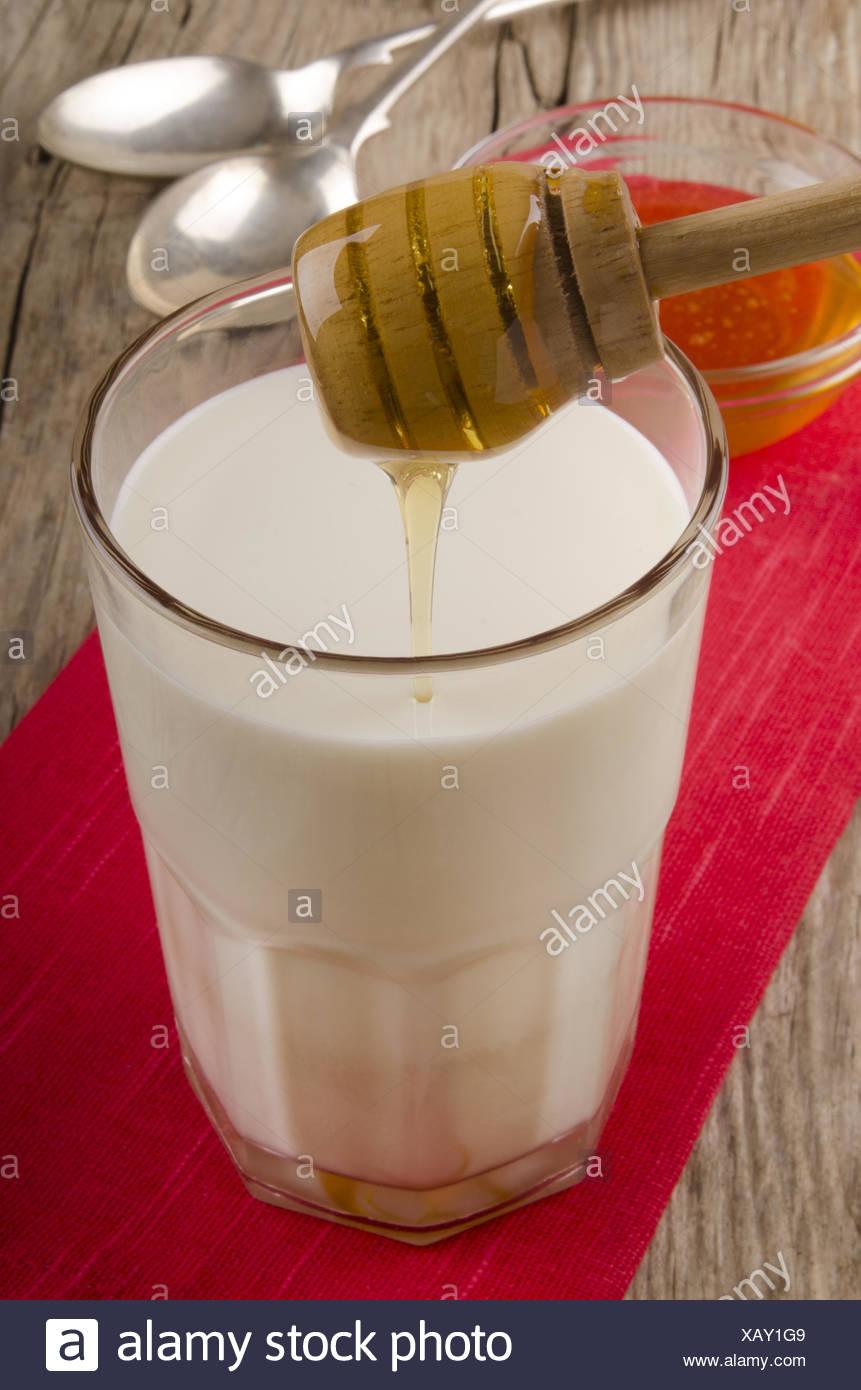 Le Miel Est Versé Dans Un Verre De Lait Chaud Photo Stock Alamy