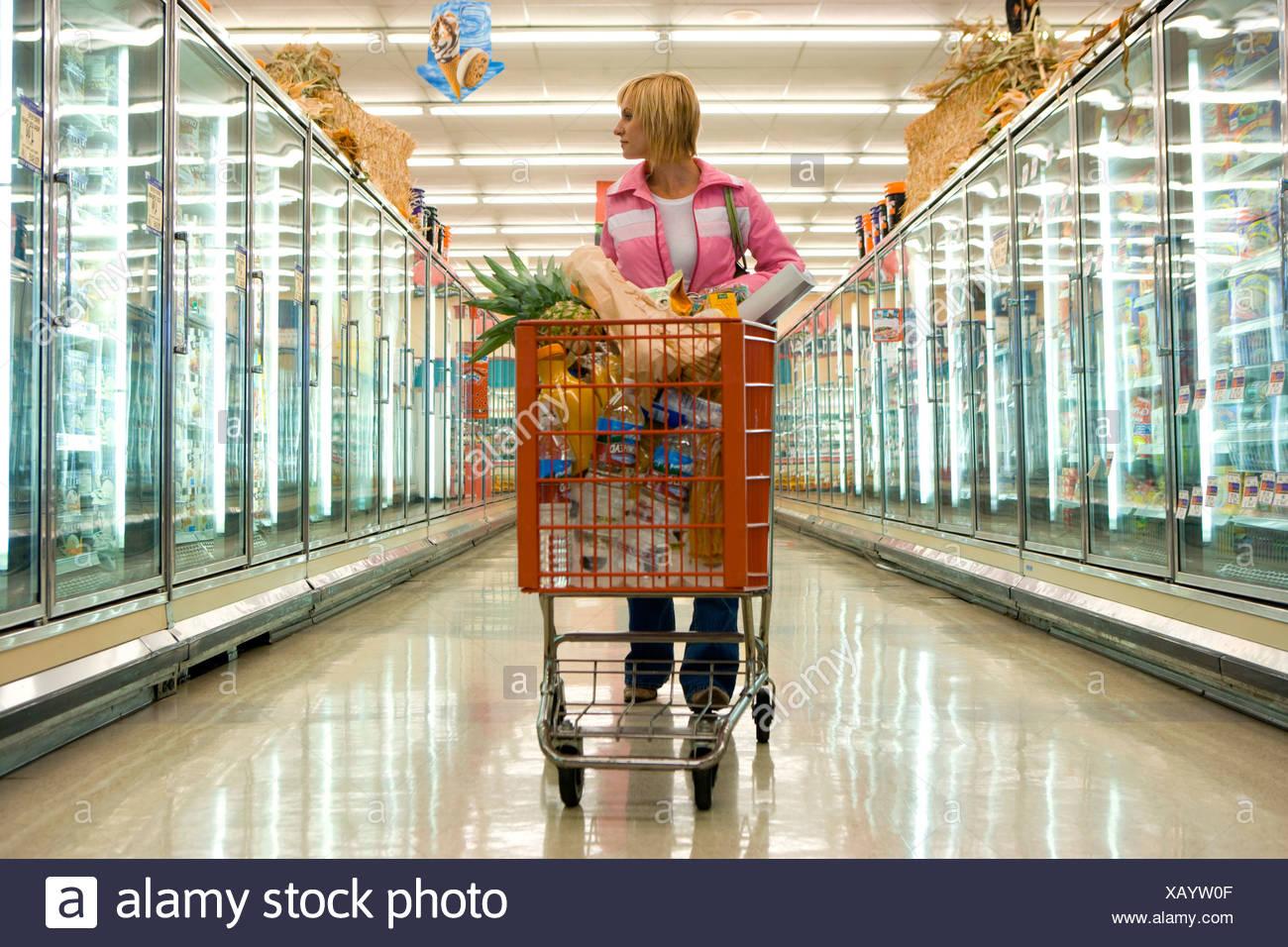 Woman grocery shopping dans la section des aliments congelés Photo Stock