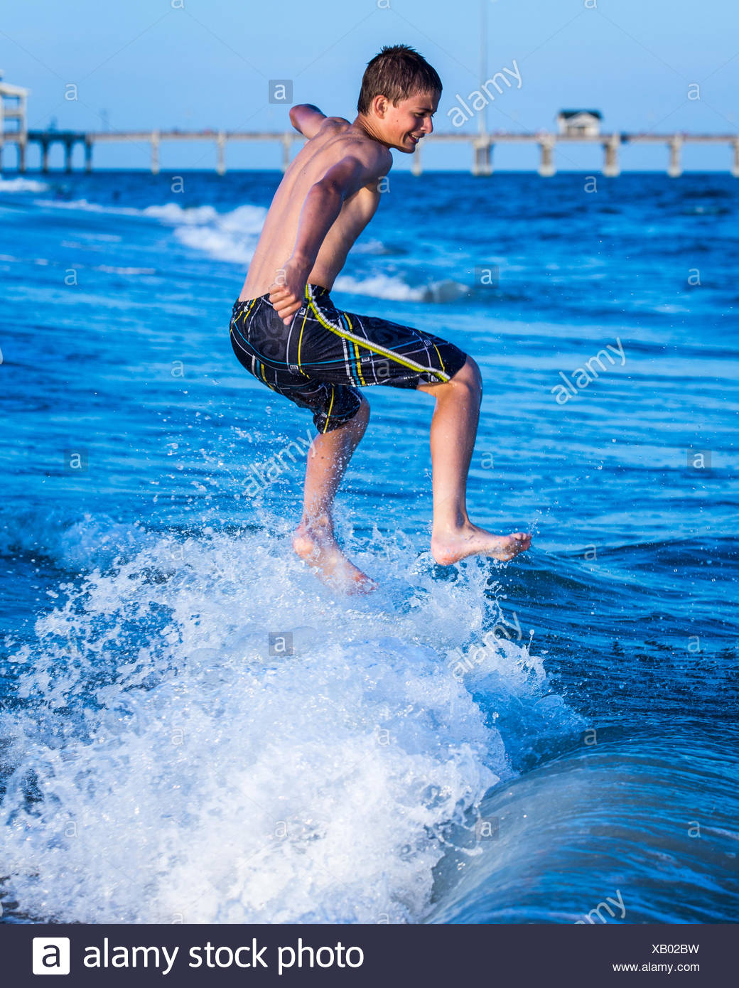Garçon sautant dans l'Océan surf Photo Stock