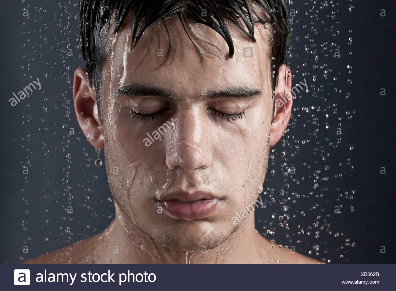 Jeune homme couvert de gouttelettes d'eau Photo Stock