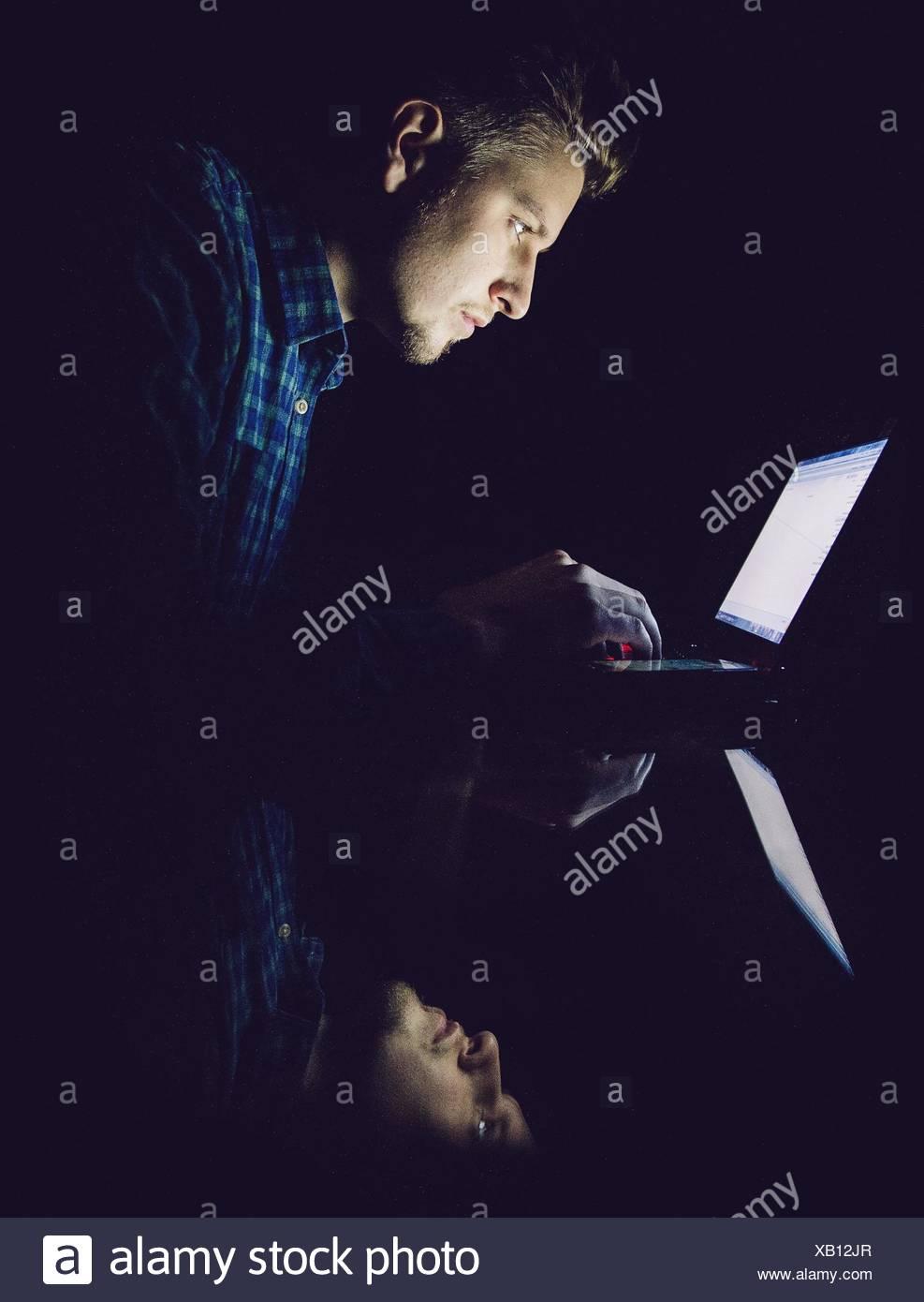 Reflet de jeune homme sur le verre pendant l'utilisation d'ordinateur portable en chambre noire Photo Stock