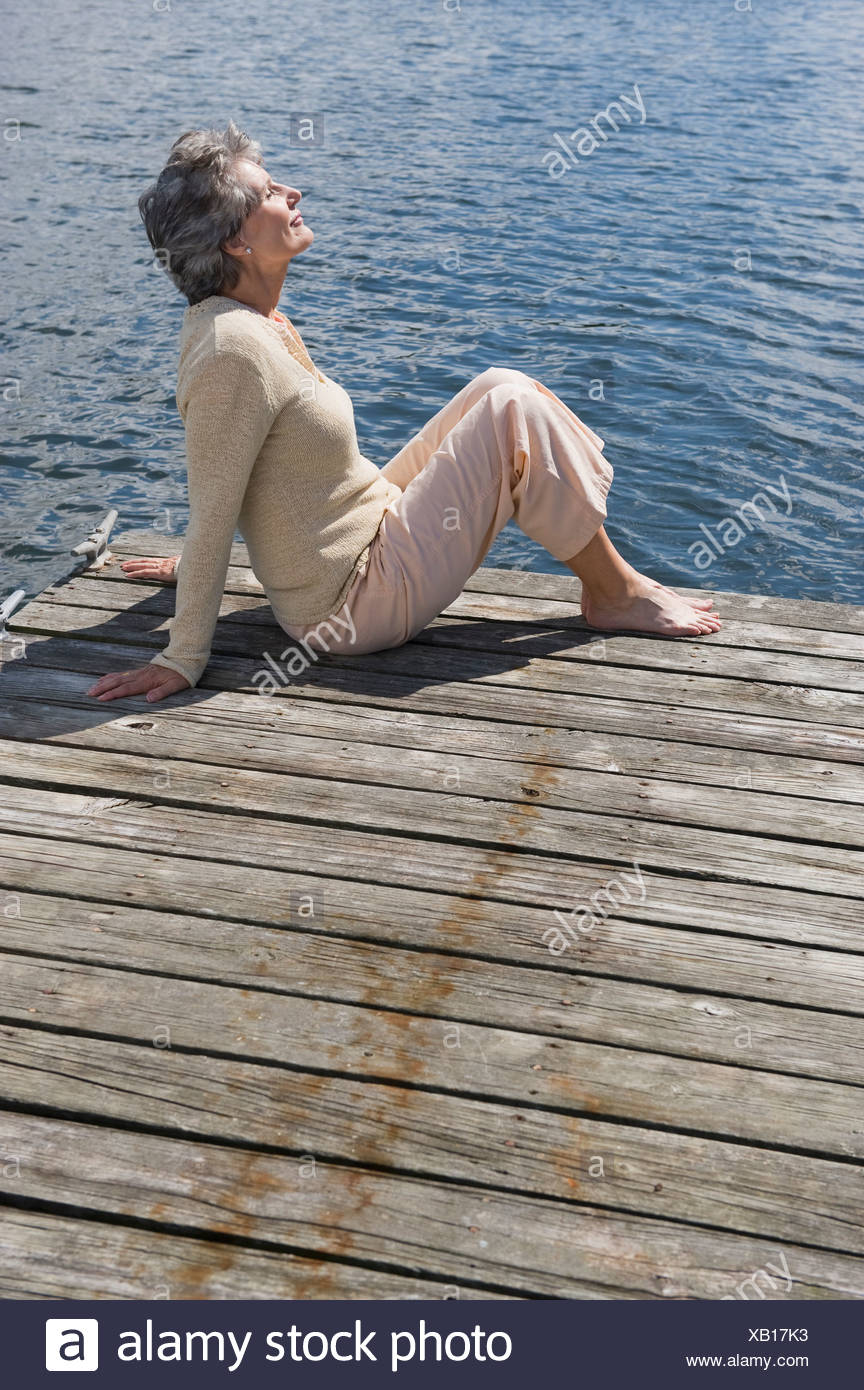 Senior woman sitting on dock Banque D'Images