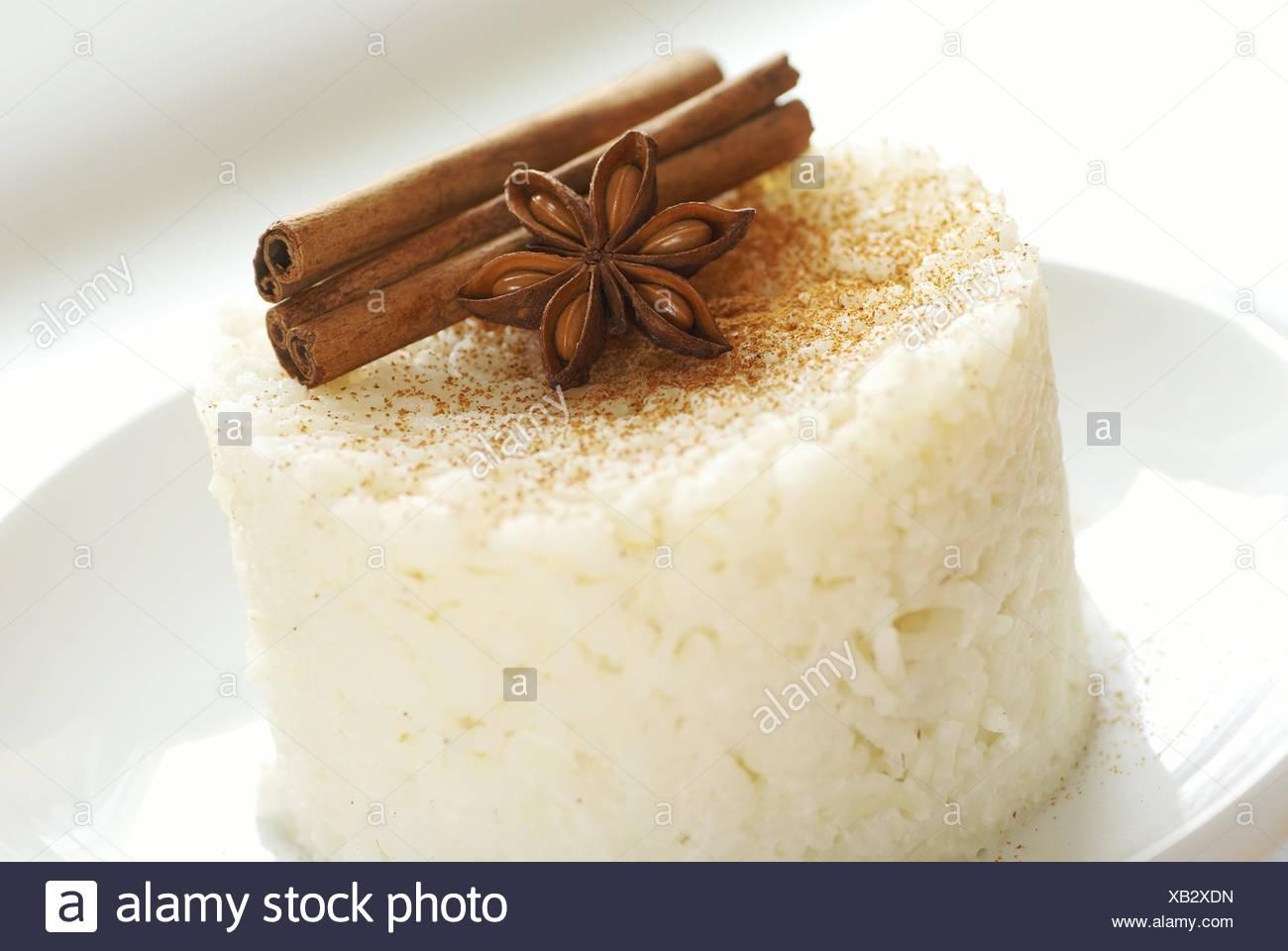 Riz au lait sucré à la cannelle sur plaque blanche. Photo Stock