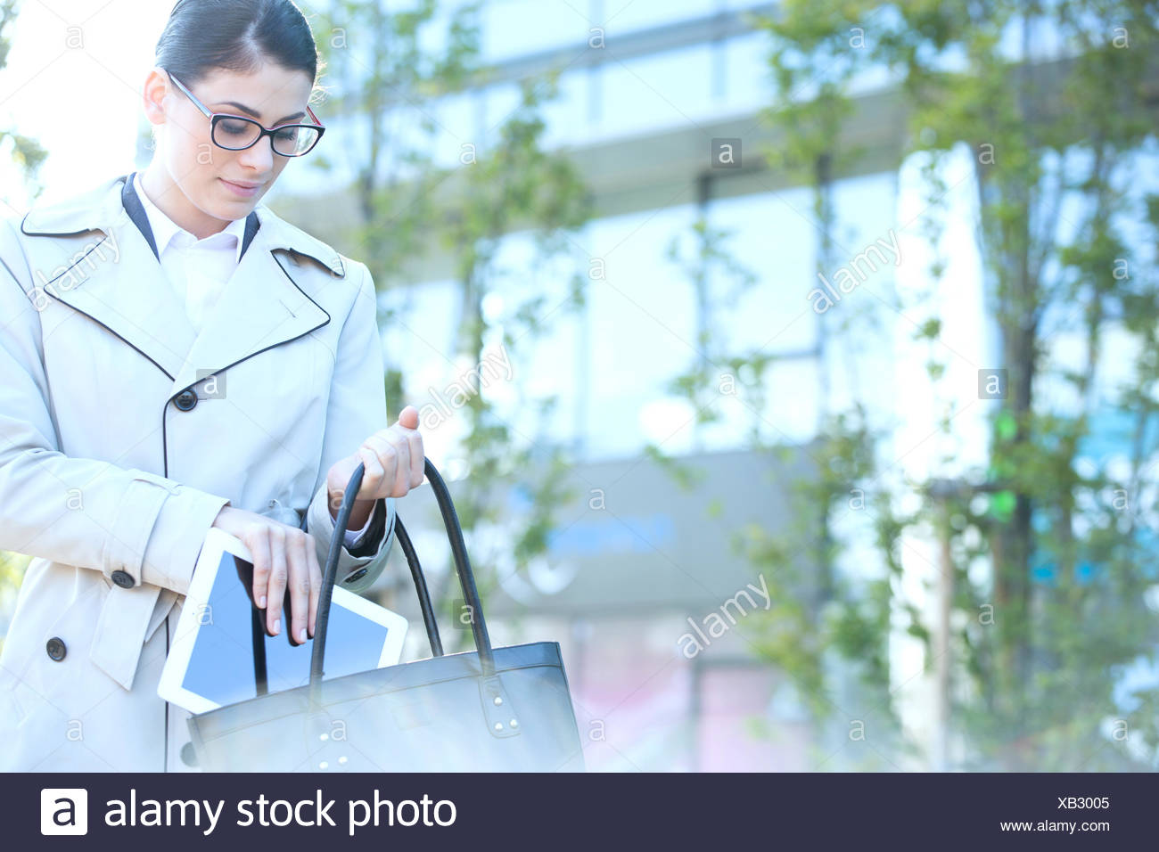 Businesswoman putting digital tablet in purse outdoors Photo Stock