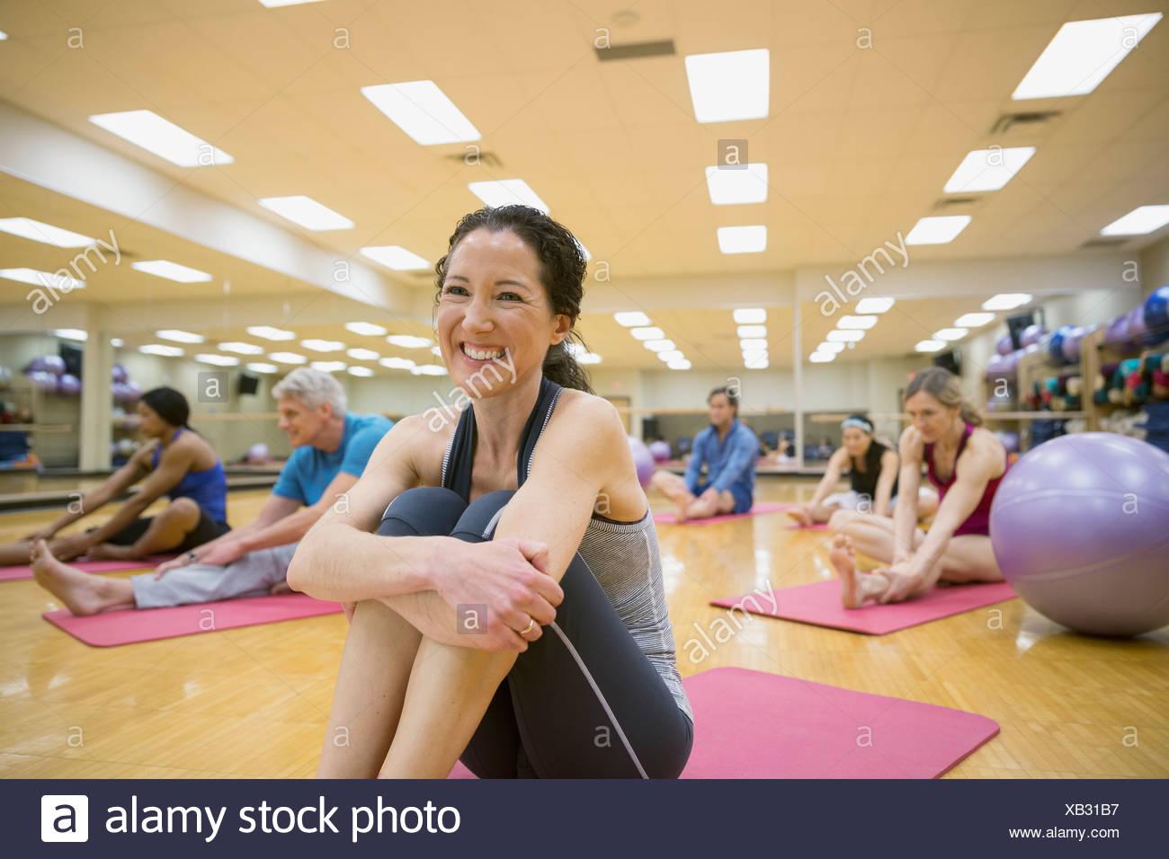 Femme sur un tapis de yoga en classe d'exercice Photo Stock