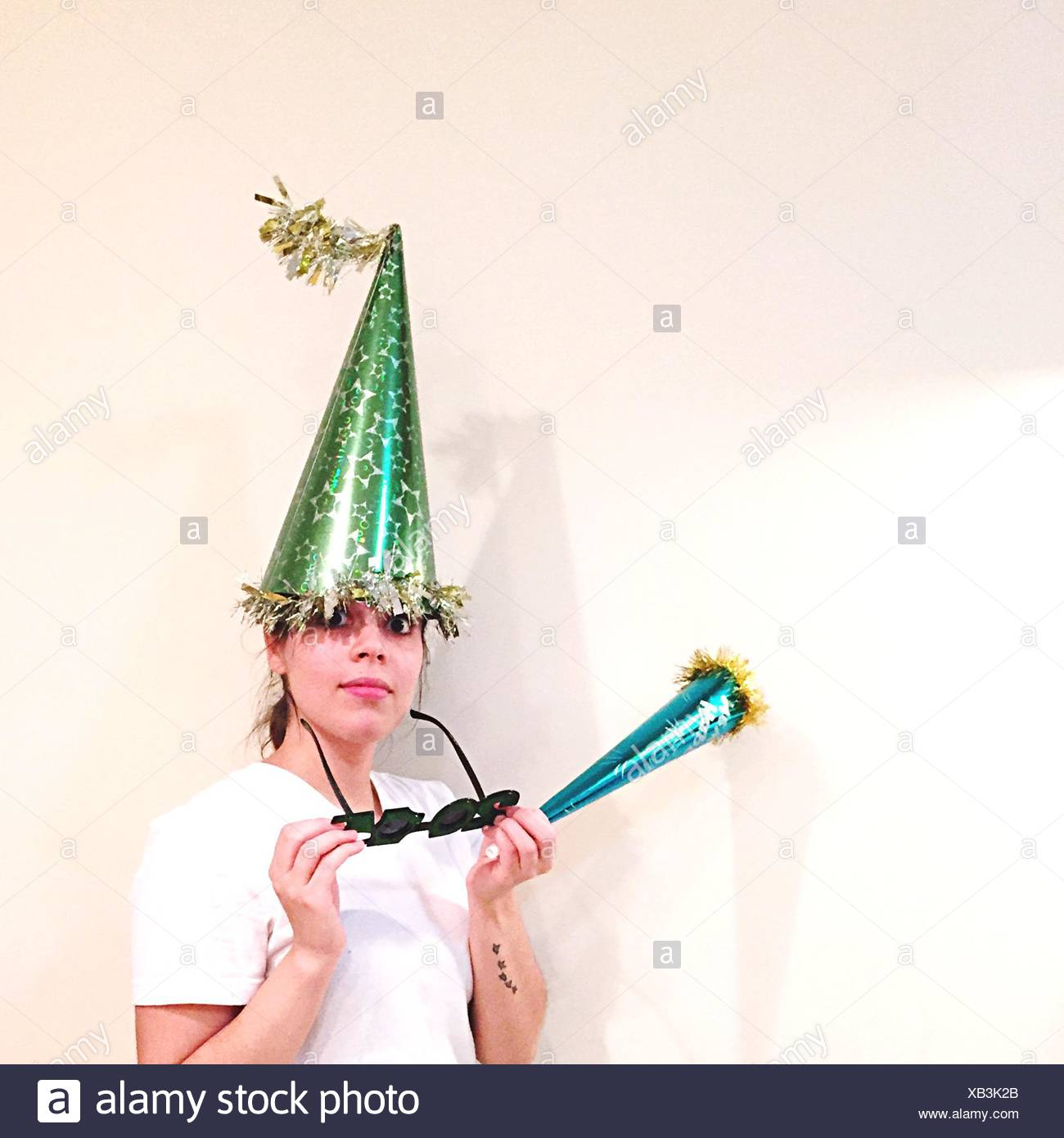 Portrait of Young Woman Wearing Party Hat Over White Background Photo Stock