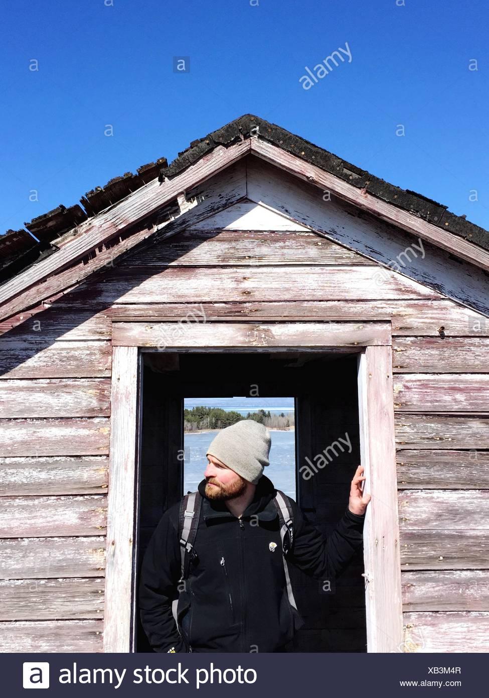 Homme debout à la porte du chalet Banque D'Images