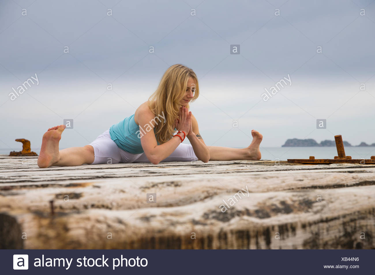 Mid adult woman with hands together practicing yoga on wooden pier mer Banque D'Images