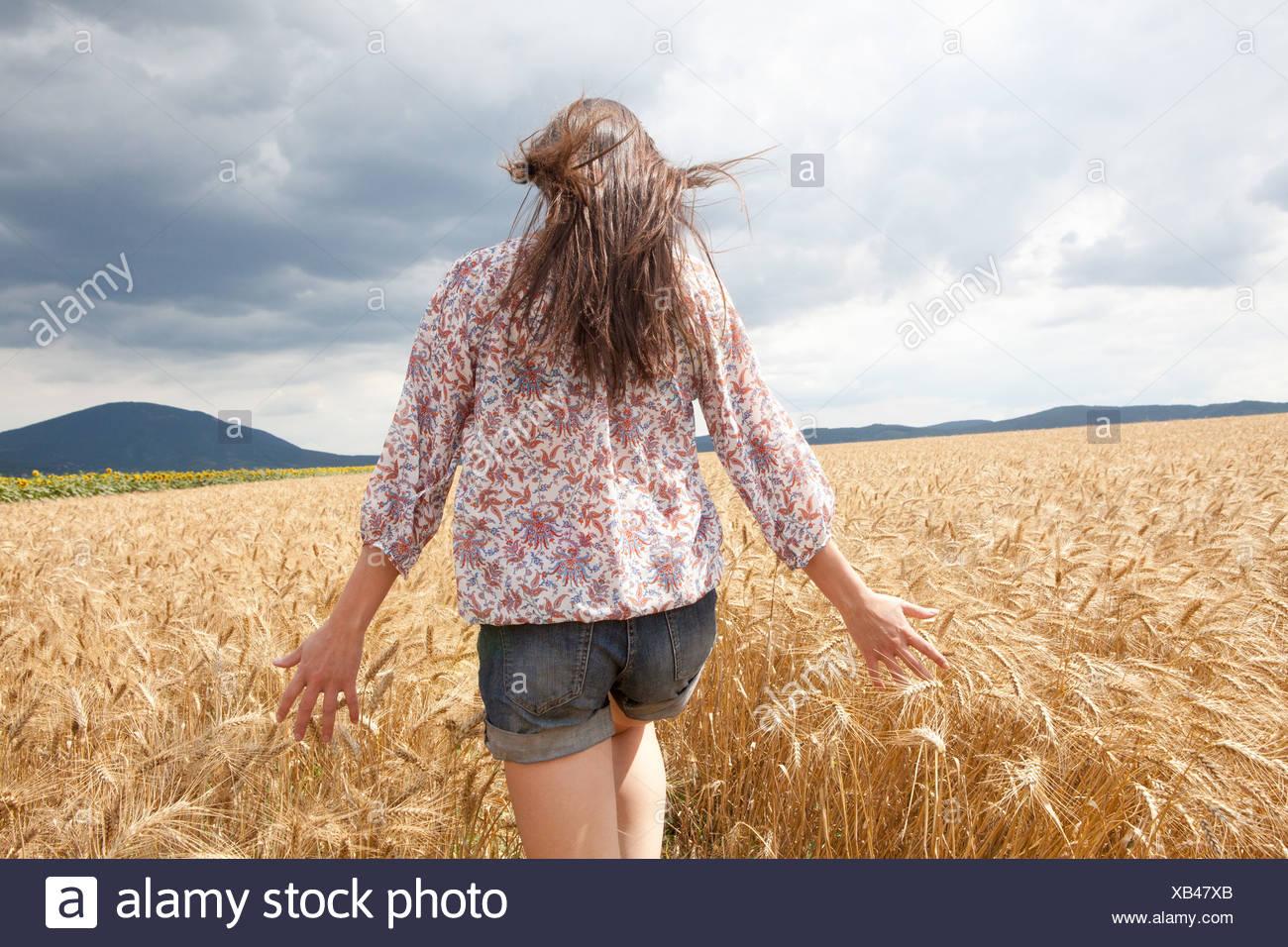 Mid adult woman walking through field Photo Stock