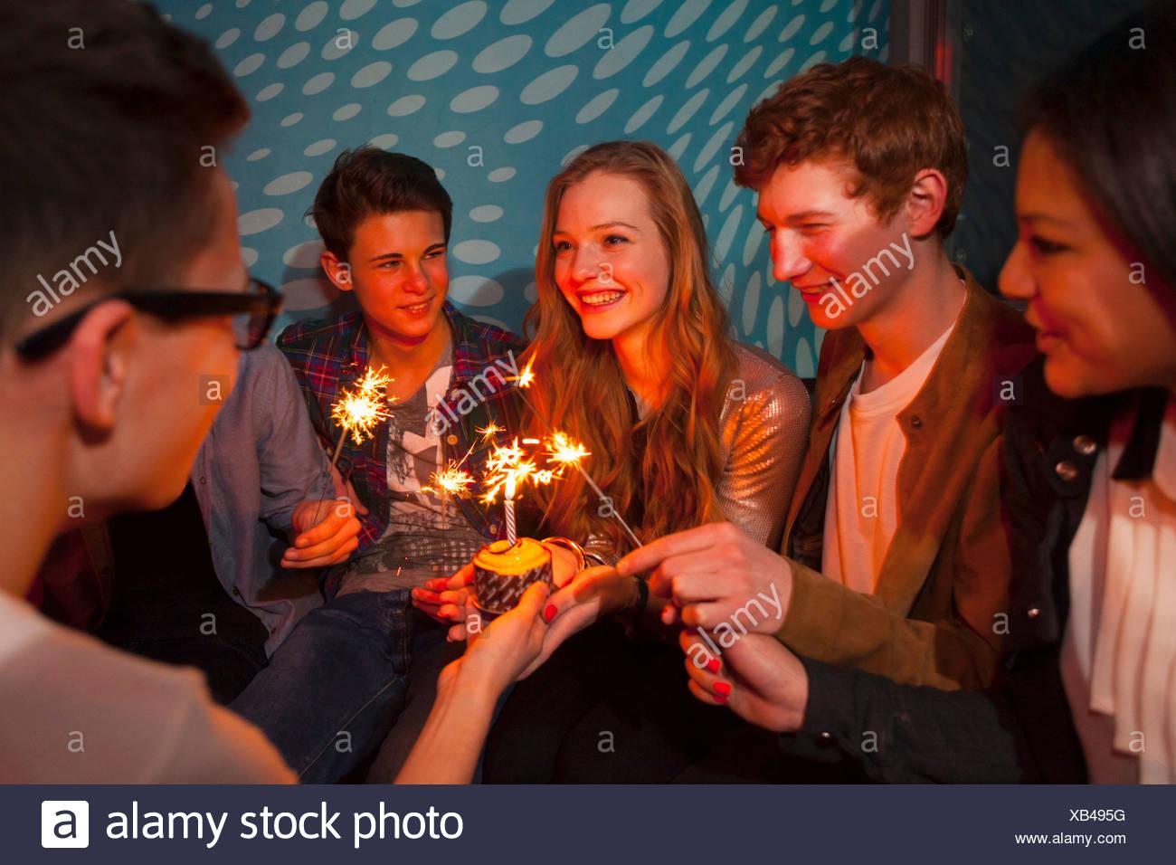 Groupe d'adolescents assis autour du gâteau d'anniversaire avec des cierges Photo Stock