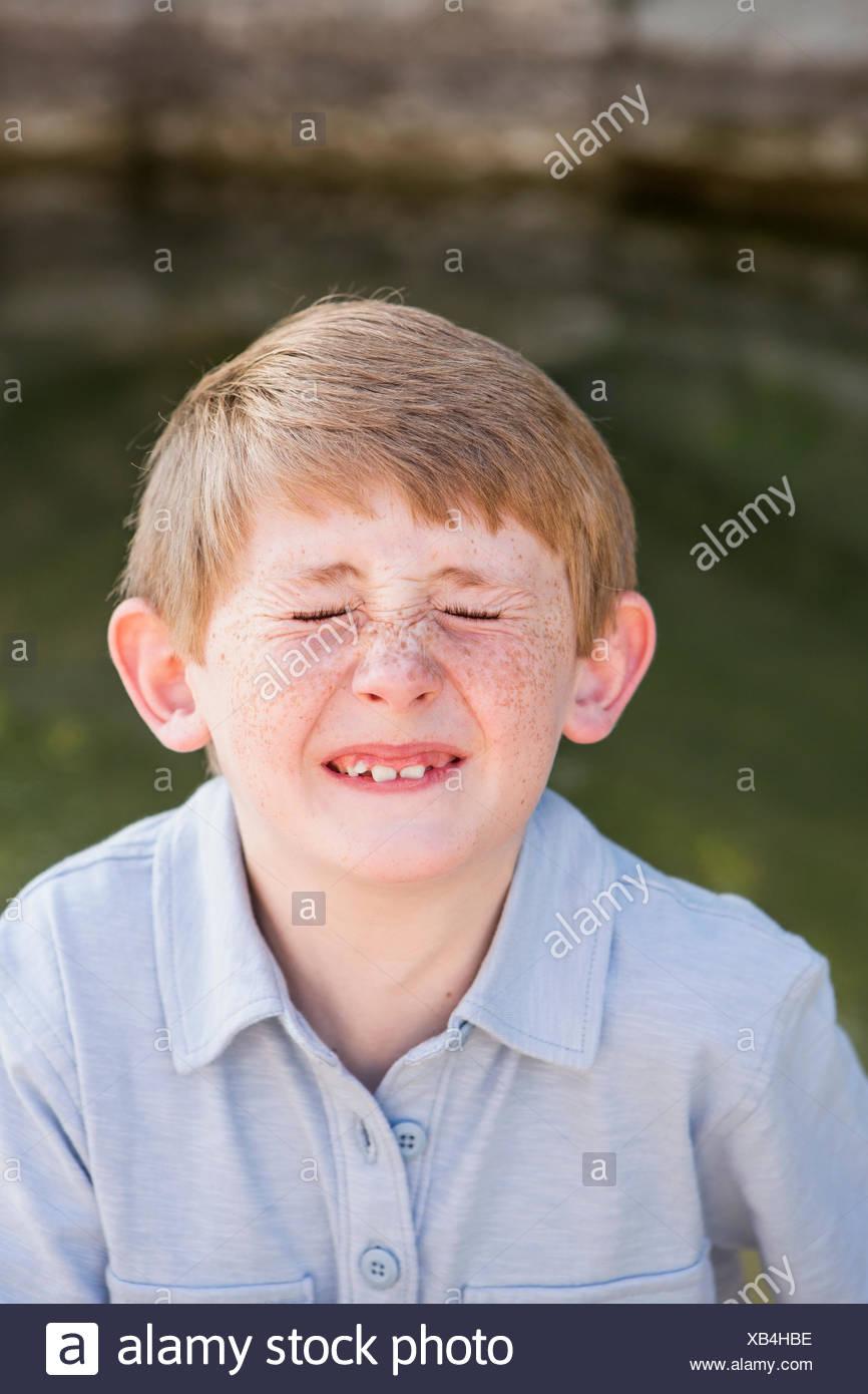 Un garçon dans une chemise bleue, vissant son nez vers le haut. Photo Stock