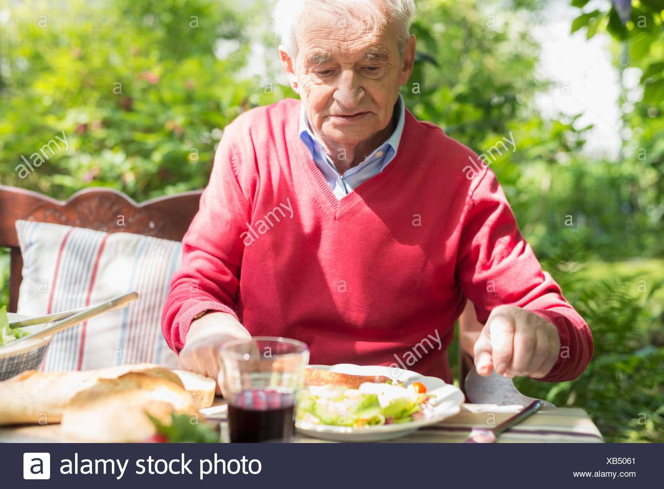 Senior man having lunch outdoors Photo Stock