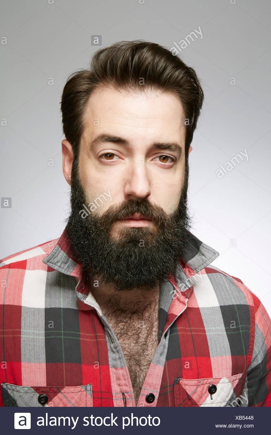 Studio portrait de jeune homme barbu à l'écart Photo Stock