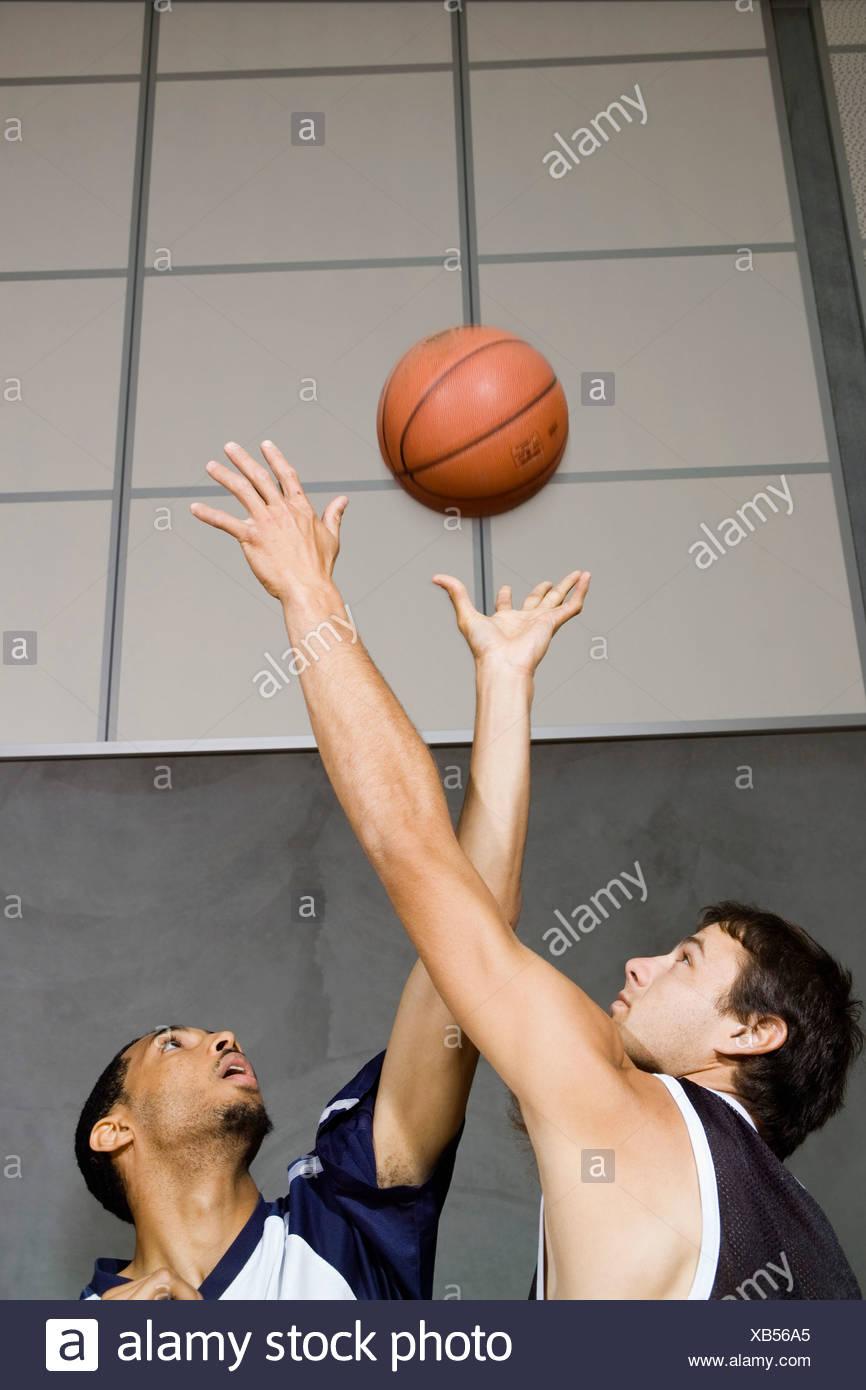 Deux joueurs de basket-ball pour atteindre un terrain de basket-ball Photo Stock