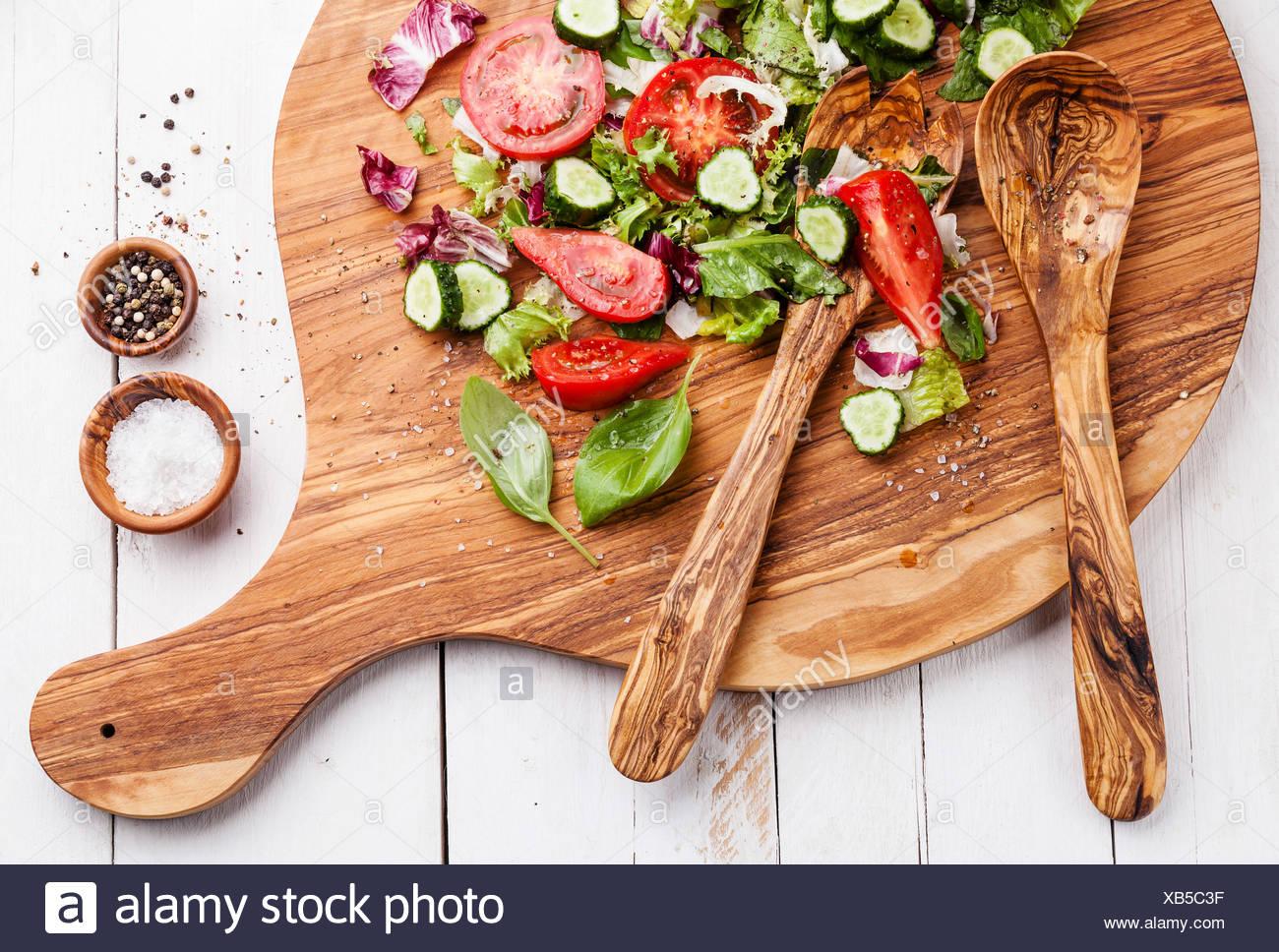 Les ingrédients d'une salade de légumes frais sur la planche à découper en bois d'olivier Banque D'Images