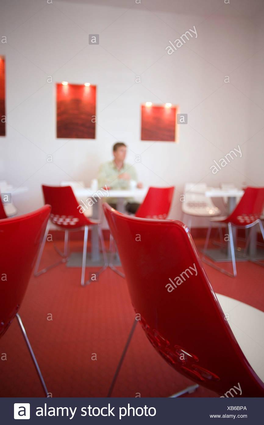 L'homme assis à table dans un café moderne avec un décor rouge et blanc, l'accent sur table et chaises en premier plan Photo Stock