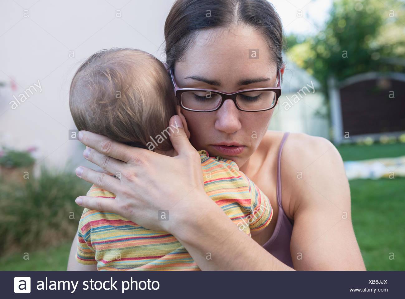 Le confort de la mère son bébé dans une pelouse, Munich, Bavière, Allemagne Banque D'Images