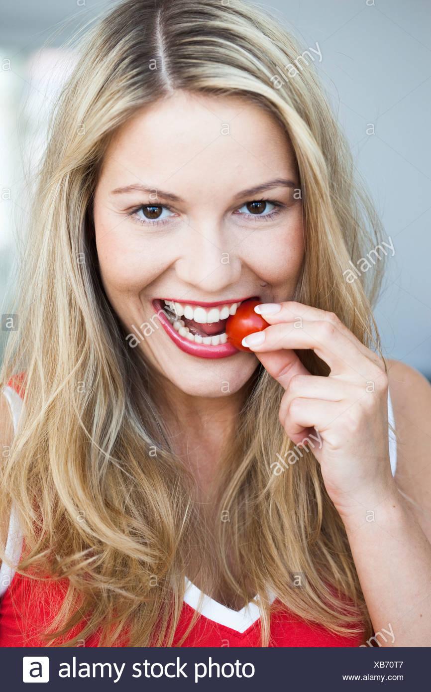 Jeune femme de grignoter sur la tomate Banque D'Images