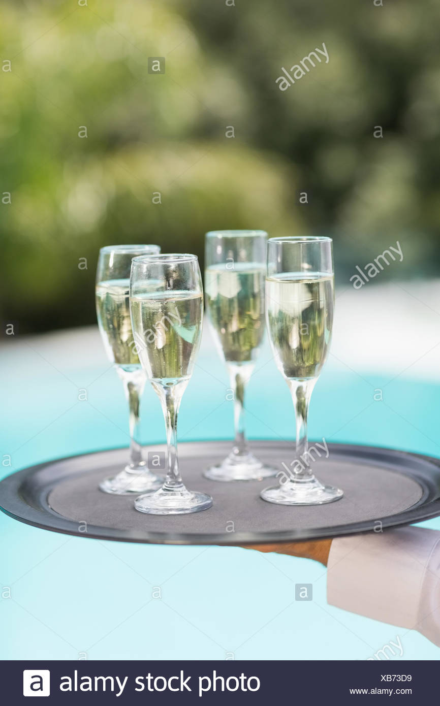 Les mains coupées de waiter holding champagne flutes le bac Photo Stock