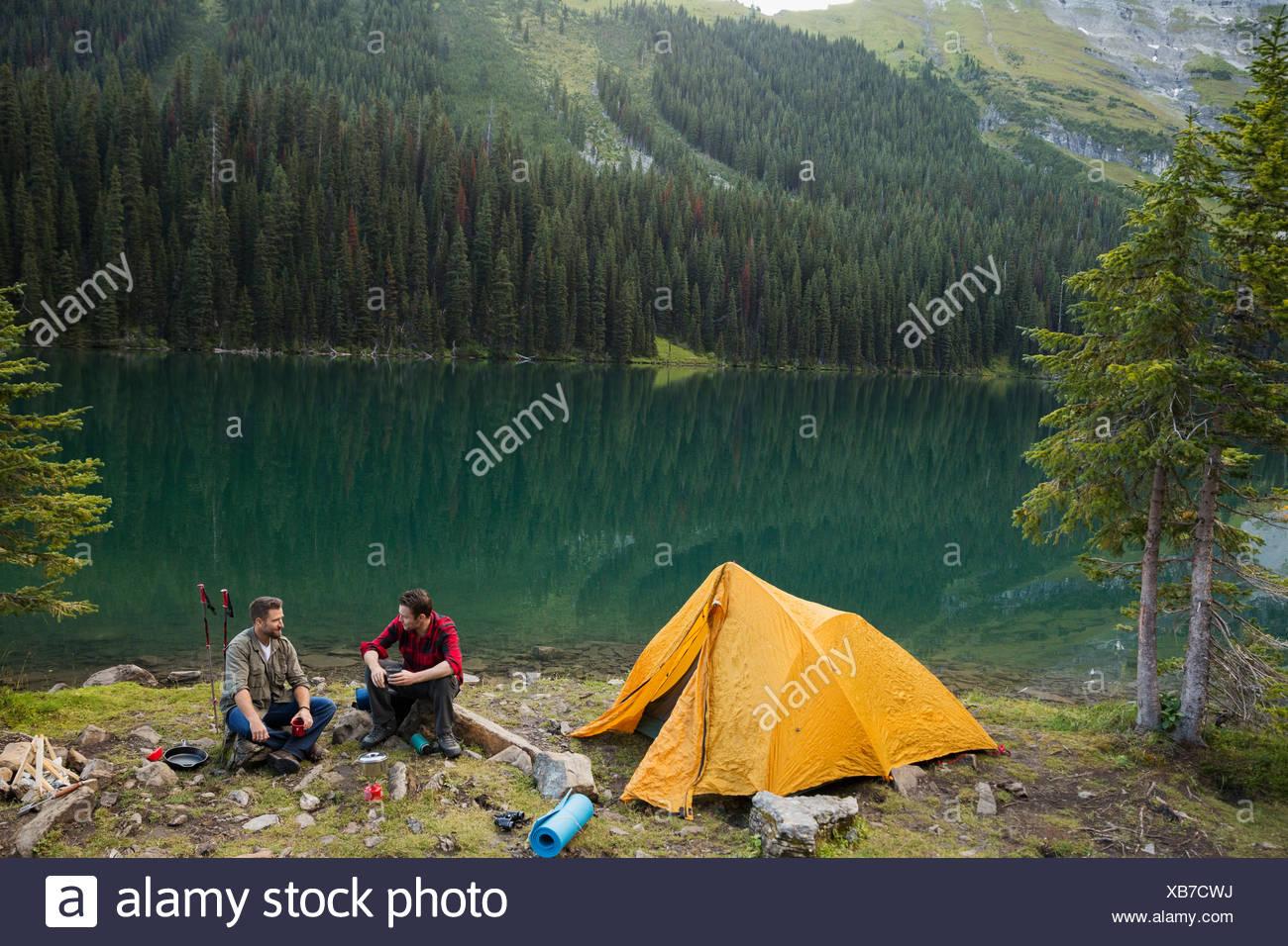 Amis du camping au camping du lac à distance Photo Stock