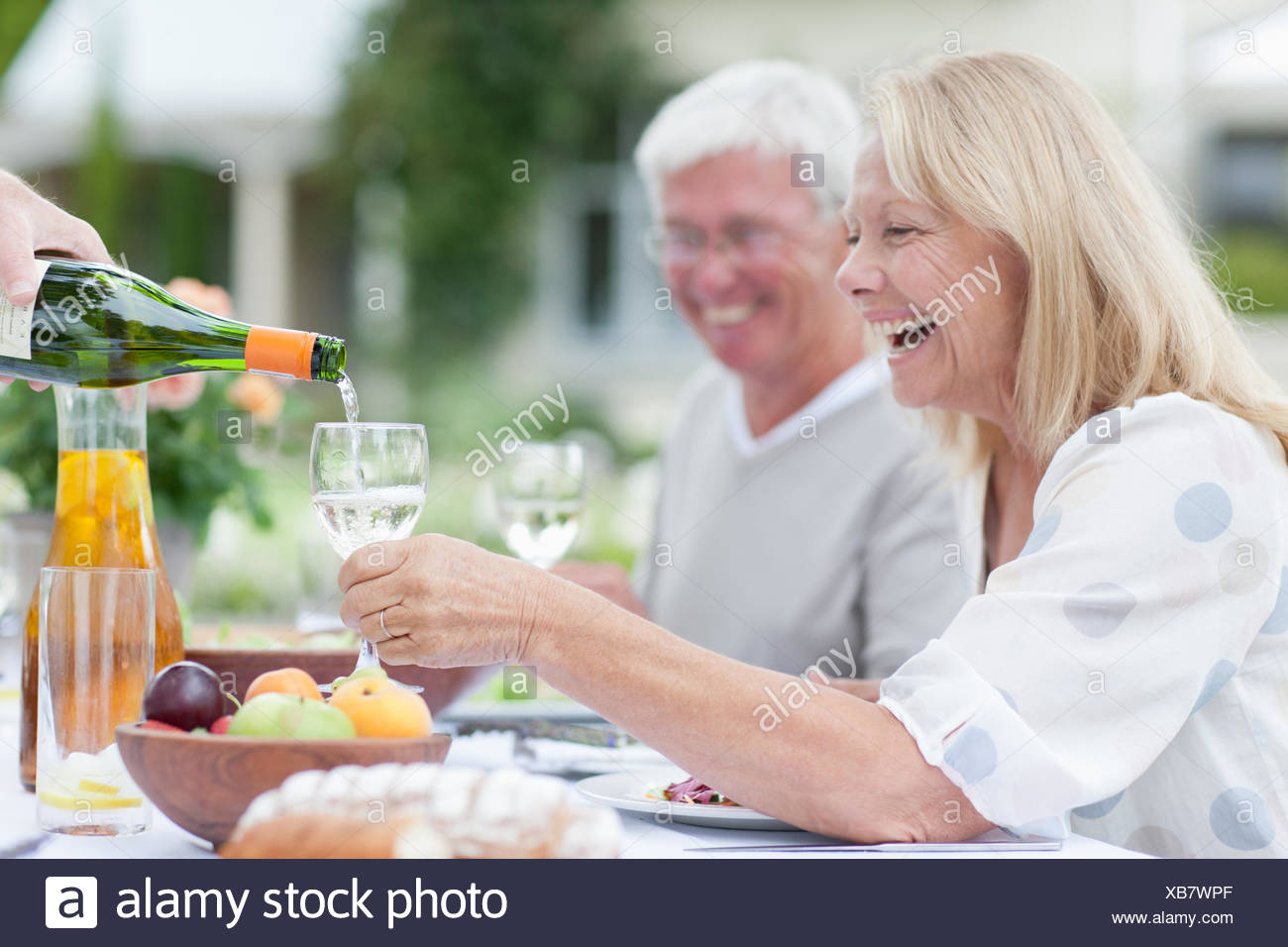 Des aînés bénéficiant du vin à table patio Photo Stock