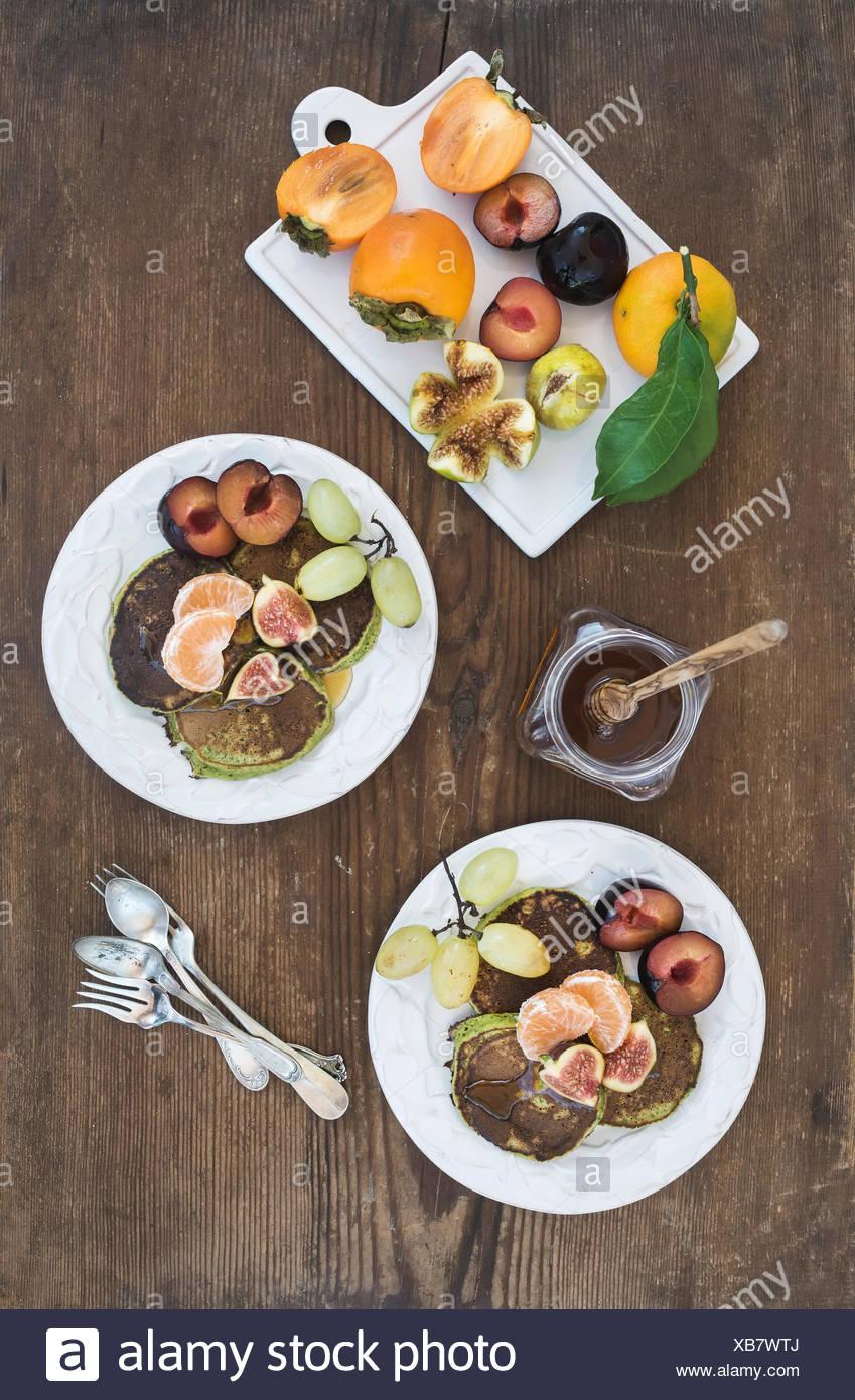 Le petit-déjeuner ensemble. Crêpes de courgettes fait maison avec des produits frais de prune, de la mandarine, des raisins, des figues et du miel dans les plaques en céramique blanc rustique plus Photo Stock