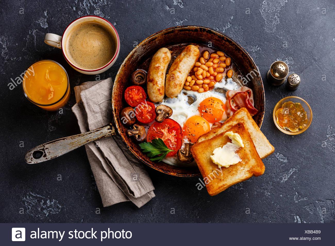 Petit-déjeuner anglais dans la casserole avec les œufs, saucisses, bacon, haricots, des toasts et du café à l'arrière-plan en pierre sombre Banque D'Images