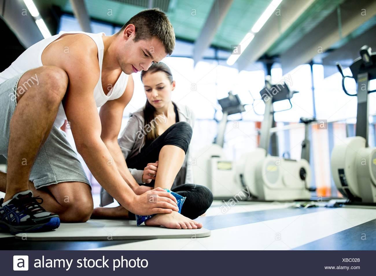 Parution de la propriété. Parution du modèle. Jeune homme l'application de glace sur la cheville de la jeune femme dans une salle de sport. Photo Stock
